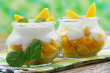Mango and yogurt desserts garnished with mint leaves