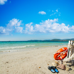 slippers and life buoy by the shore in Alghero