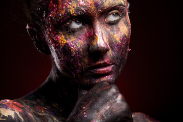 Girl with colorful make-up posing in dark