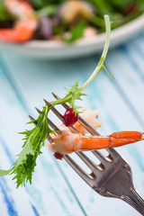 Fresh prawn, salad leaf and pomegranate seed on fork