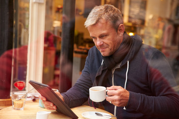 Man Viewed Through Window Of Cafe' Using Digital Tablet