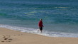 Woman Running on Beach with Waves in the Background