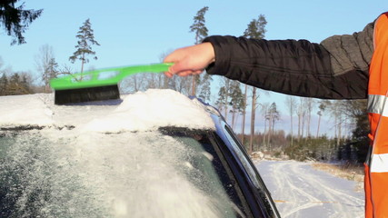 Man on the road cleans with brush the car out of the snow