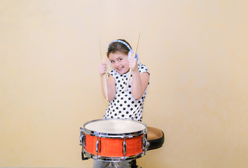 little happy joyful girl in motion sitting behind a snare drum