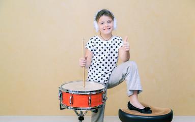 fashionable joyful little girl standing behind a snare drum