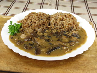 Buckwheat with mushrooms on plate - vegan meal. Front view.