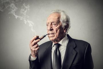 Elderly businessman smoking the pipe
