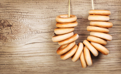 Bagels on rope over wooden background