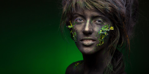 close-up portrait of woman in black paint and green leaf on face