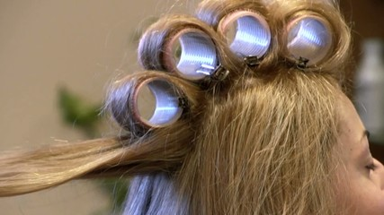 Hairdresser making curls on head of client at the hair salon