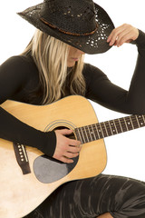 woman with guitar and cowboy hat sit
