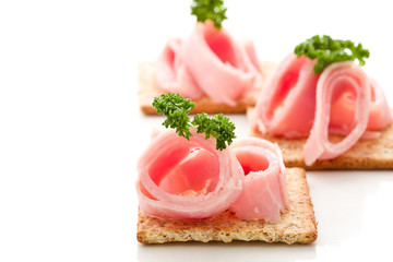 Crackers canapes with ham and parsley