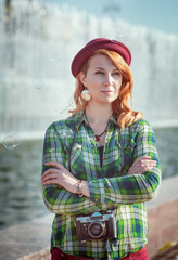 Hipster redhead girl in hat with retro camera