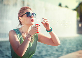 Beautiful young girl in vintage clothing blowing bubbles