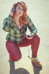Hipster redhead girl with headphones listening music