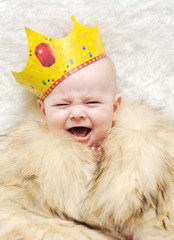 child in a fur cape and crown on a white background. baby crying