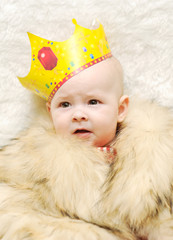 child in a fur cape and crown on a white background