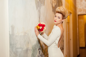 bride in white and red dress with a bouquet in a beautiful room