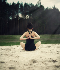 beautiful girl is engaged in yoga in the forest on the sand