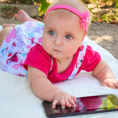 A small child lying on her stomach, playing with a tablet.