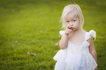 Adorable Little Girl Wearing White Dress In A Grass Field