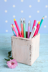 Holder with pens and pencils near flower