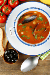 Tasty soup with mussels, tomatoes and black olives in bowl