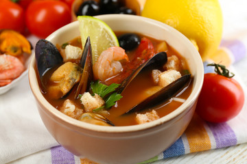Tasty soup with shrimps, mussels, tomatoes and black olives in