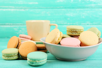 Assortment of gentle colorful macaroons in colorful bowl and