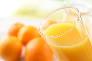 Glass of orange juice and oranges on wooden table background