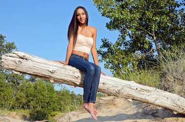 attractive young woman on beach log