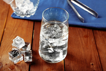 Glass of water with ice on napkin on wooden table background