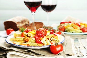 Pasta salad with vegetables and two glasses of red wine