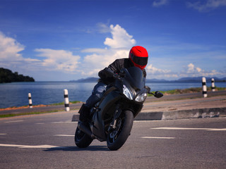 young biker man riding motorcycle on asphalt road against beauti