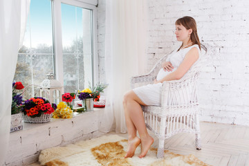 Pregnant women sit on a chair relaxing near window