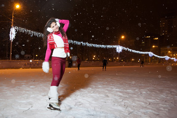 beautiful girl on a skating rink in the winter evening