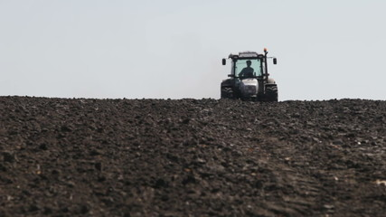 tractor leaves the horizon plowed field