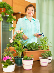 Mature woman working with flowers in pots