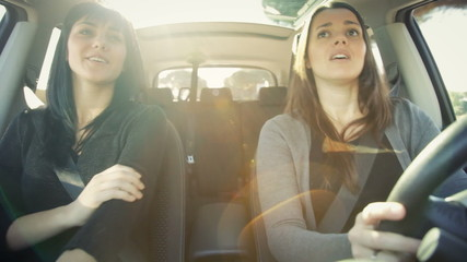 Happy female friends driving car laughing