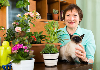 Portrait of mature woman with decorative plants and cat