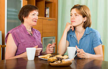 Young girl and her pensioner mother drinking coffee