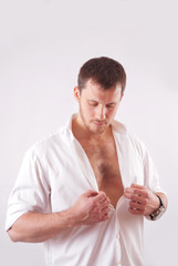 Young man with beautiful face, dressed in white unbuttoned shirt