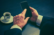 phone and cup of coffee in hands of businessman in dark colors
