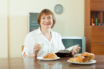 mature  woman having breakfast with milk at home