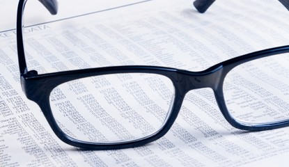 business financial newspaper report see through glasses lens