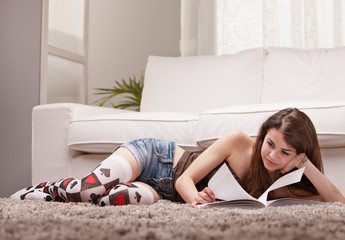 pretty girl reading a book on her rug