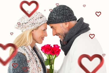 Smiling couple in winter fashion posing with roses