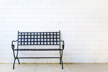Black metal bench with white wall