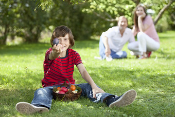 Deutschland, Junge hält Ostereier mit den Eltern im Hintergrund