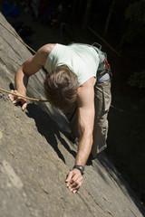 Junger Mann Bergsteigen in Kletterwand